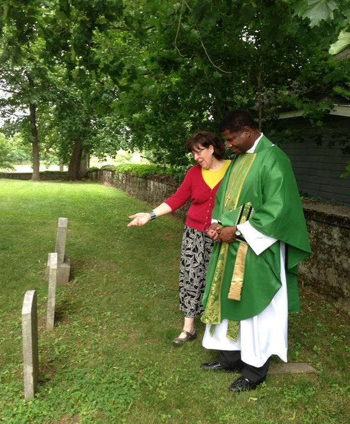 Emilie Amt and the Bishop of Maryland look at historic African-American graves in the cemetery at St. Mark's Episcopal Church, Lappans, in Washington County, Maryland.