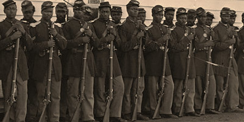 Line of African American soldiers in Civil War uniform standing with rifles